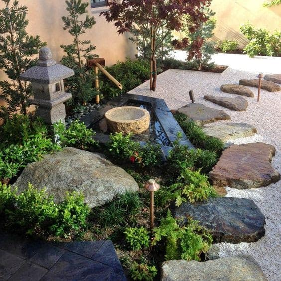 Zen corner with fountain with sculptures, pebbles and rocks
