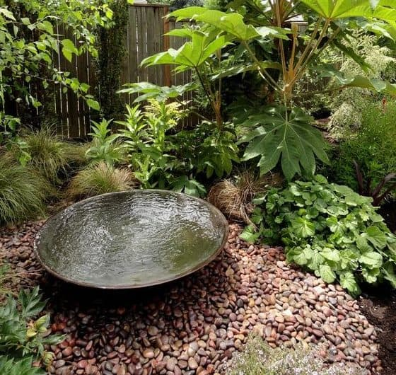 Pebbles and water feature that help attract some birds to the garden
