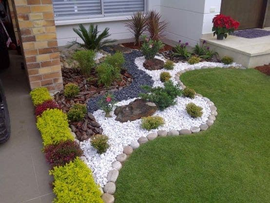 Large pebbles used as a border between the bed and grass