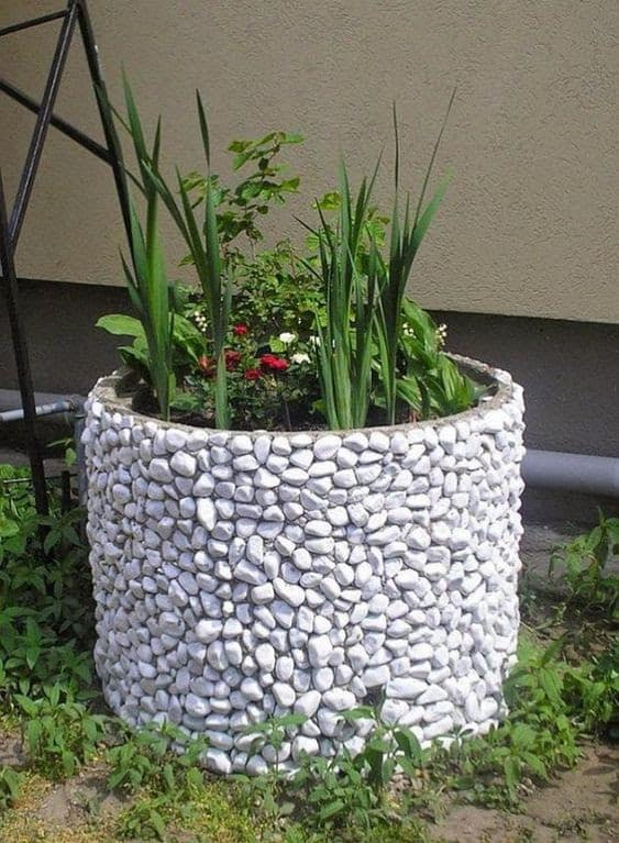 An old planter decorated with white pebbles