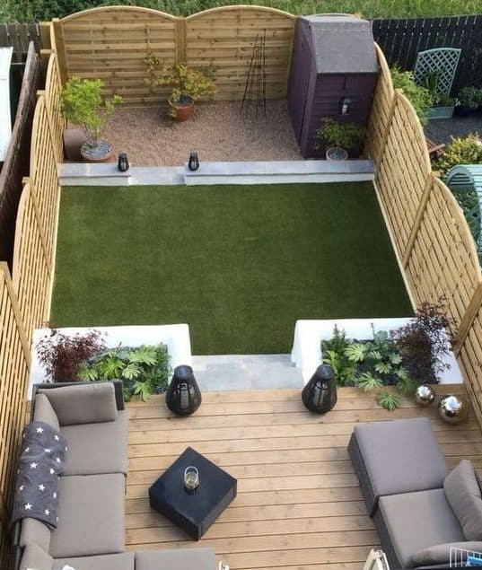 A stylish deck with comfy sofas and a shed in the corner of the garden