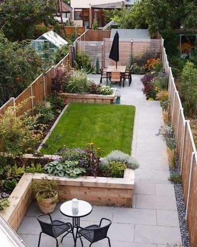 Narrow garden with grass with raised flower beds