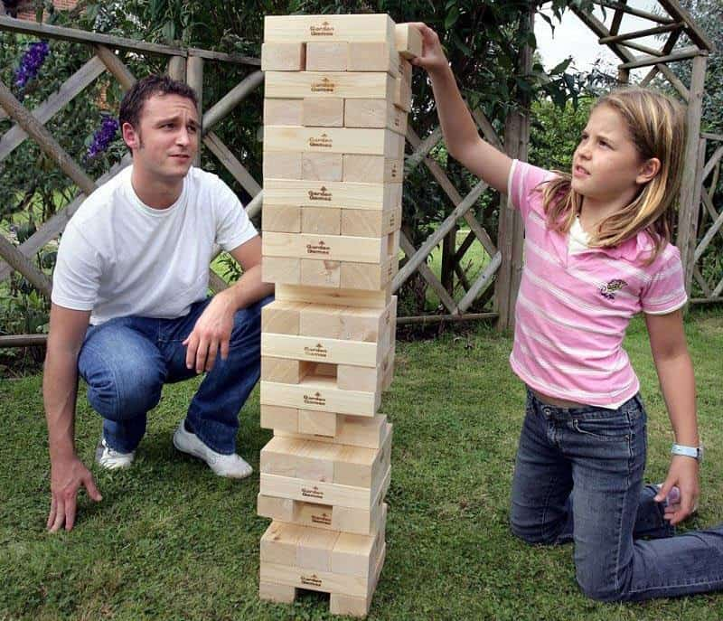 Father and daughter playing giant jenga outdoors