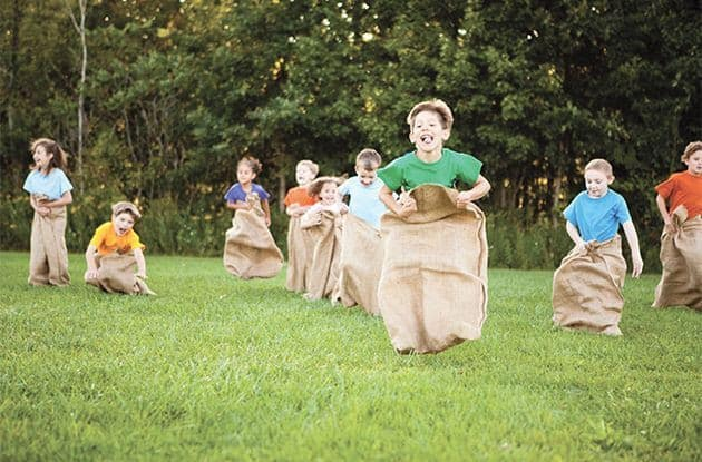 Kids having fun while playing potato sack race