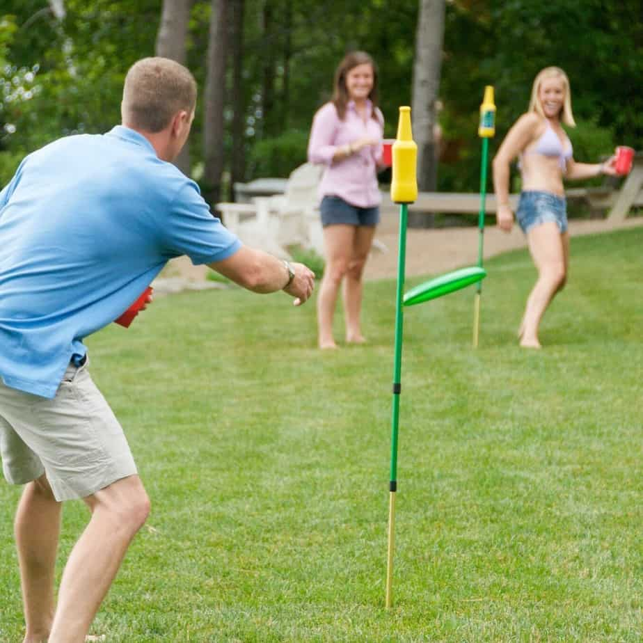 A family playing bottle bash in the yard
