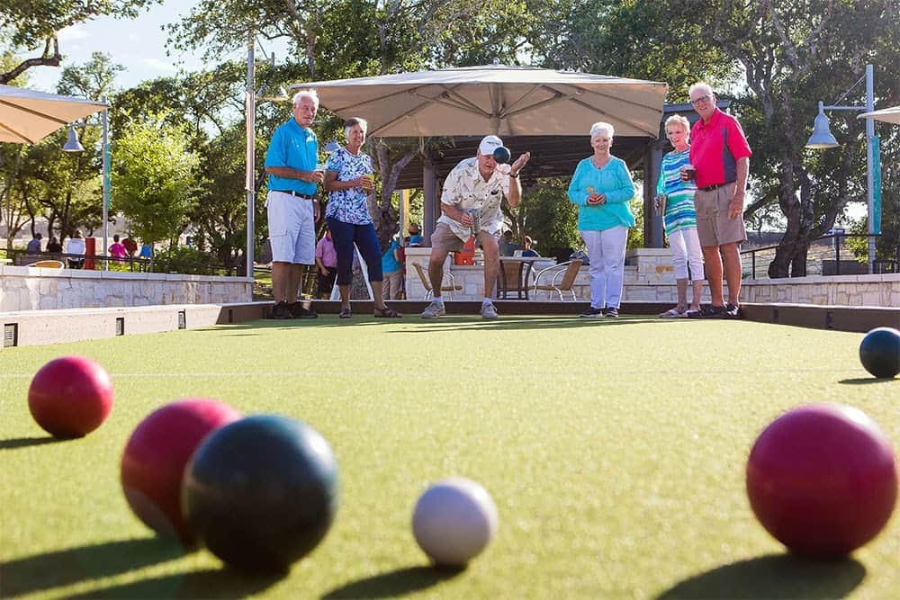 Adults playing bocce ball in a courtyard