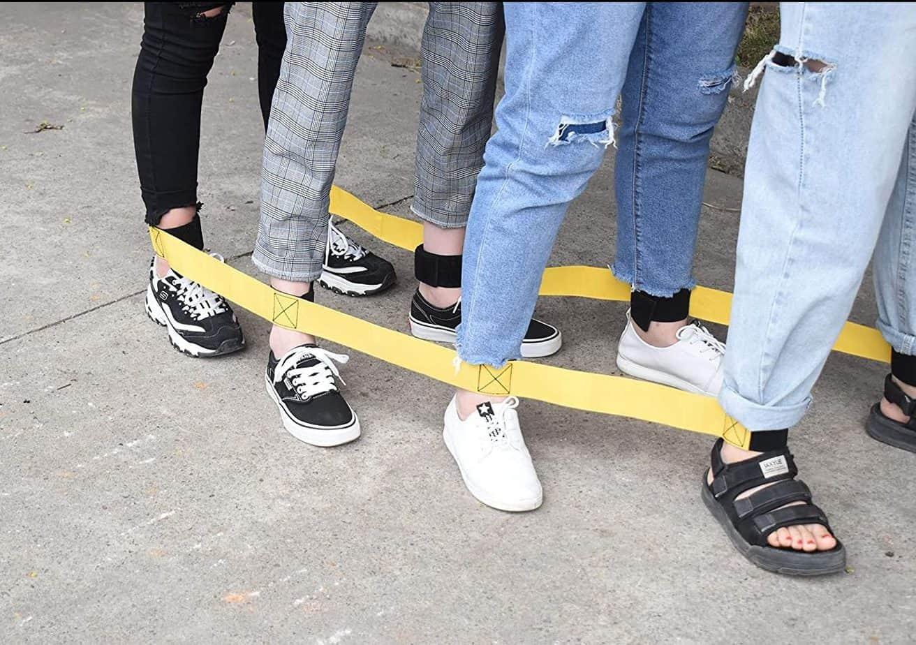 Teenagers playing 4-legged race bands