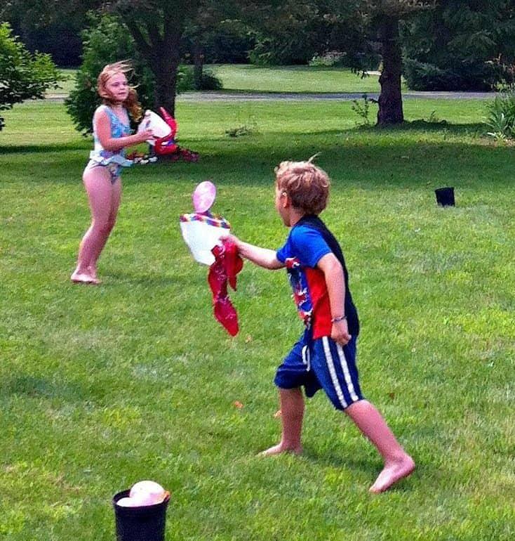 Children playing milk jug water balloon toss in the garden