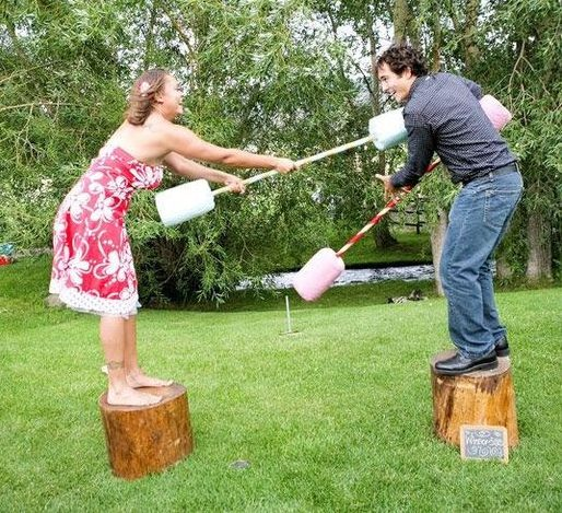 Two players playing pool noodle gladiators while stepping on log stepping stones