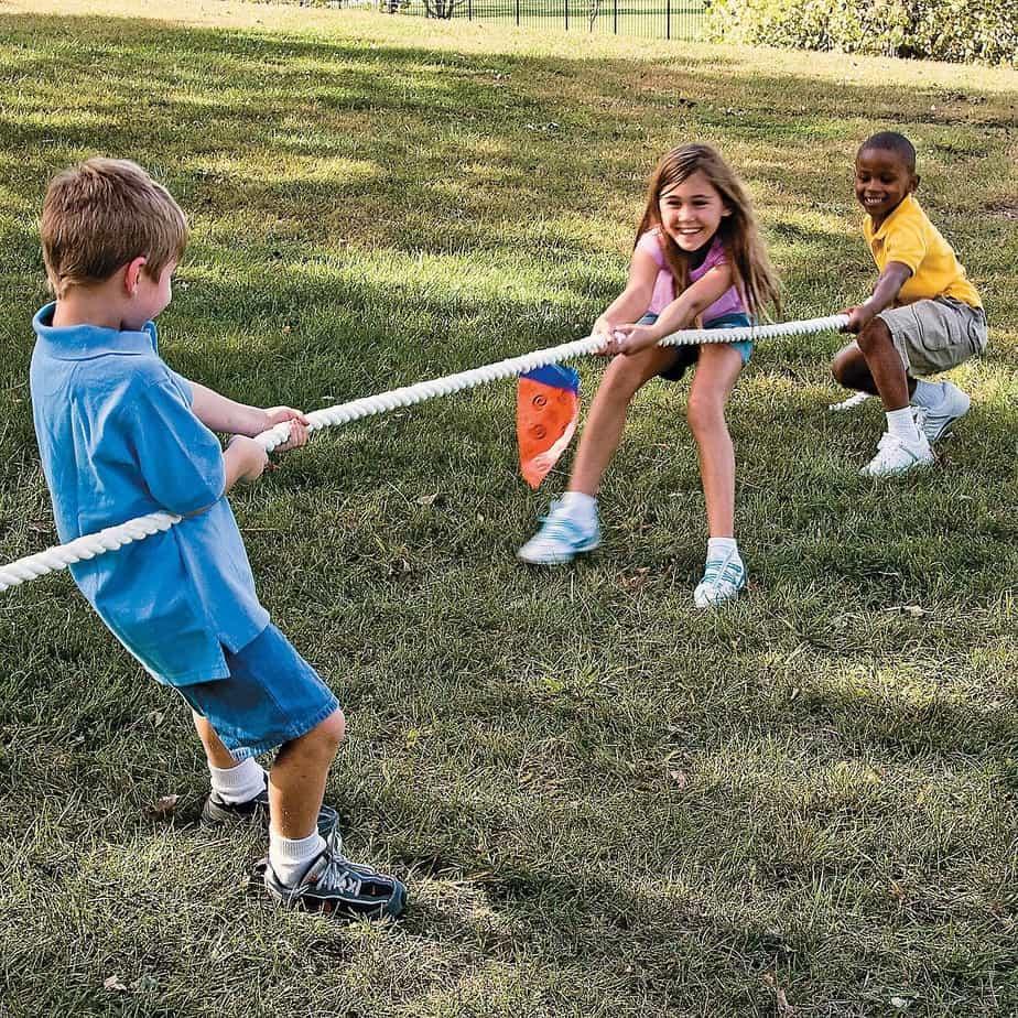 Children playing tug of war in the backyard