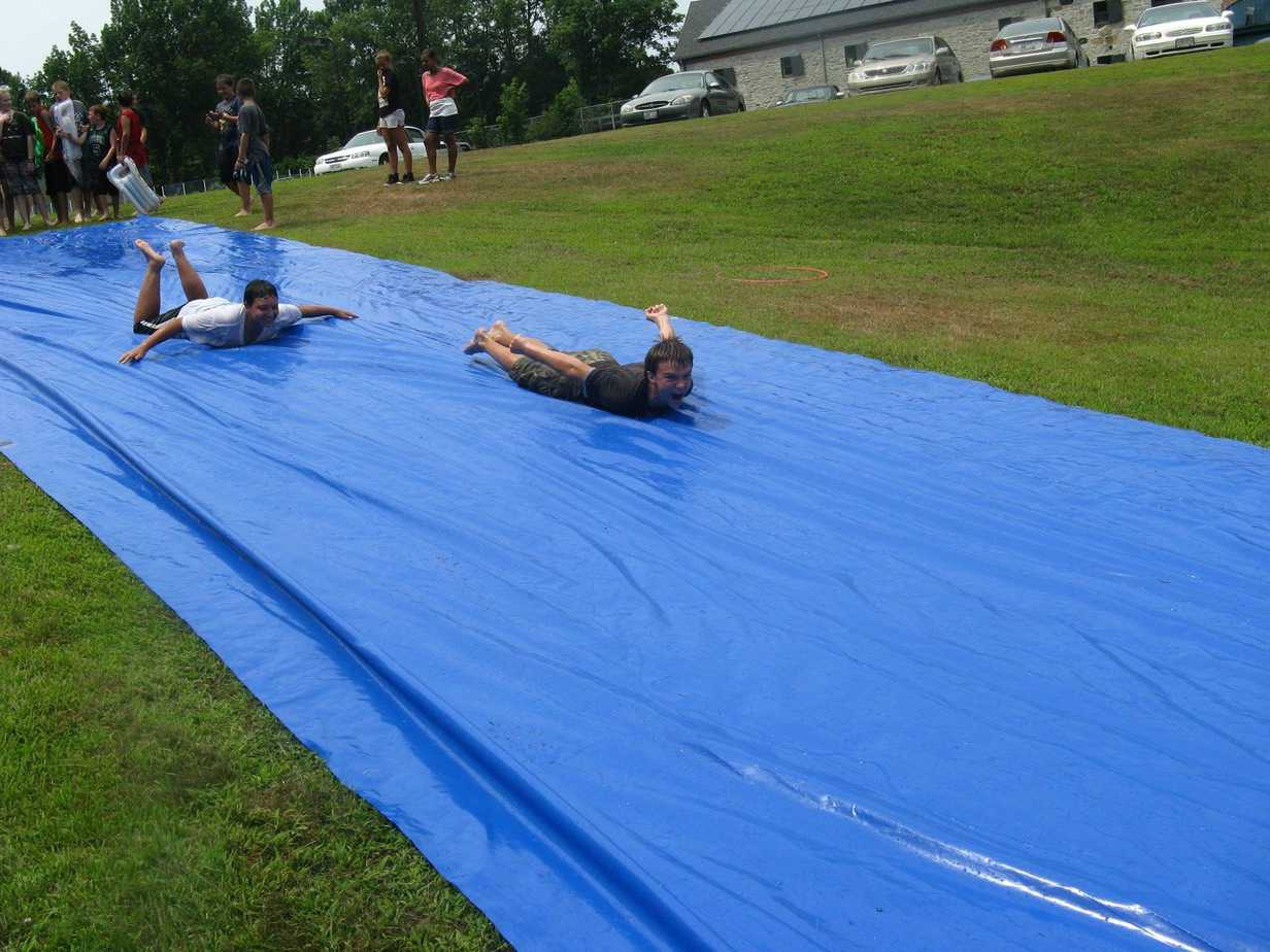 Children playing slip and slid in the garden with a big blue DIY slide