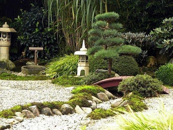 A rock creek and a dry gravel garden space under a garden bridge