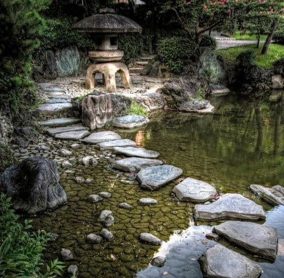 Stepping stones on river with a large stone pagoda as a focal point
