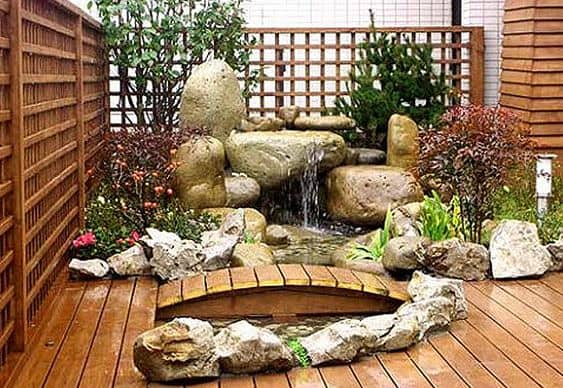 Bridge on wooden deck with a dramatic stone water feature