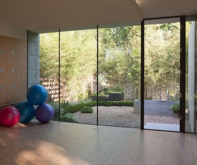 A garden gym with large windows offering a view of the yard