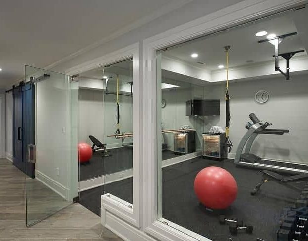 A combination of mirrors and glasses separating the rooms in a garden gym