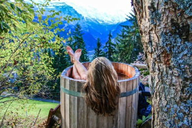 A woman enjoying an outdoor bath with a small wooden tub in the mountains