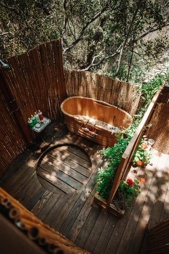 A wooden outdoor hot tub in a bamboo-theme outdoor bath