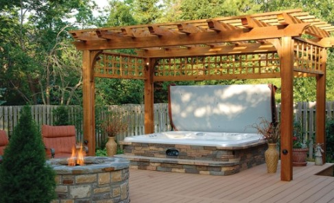 A stone-made outdoor hot tub in a garden gazebo