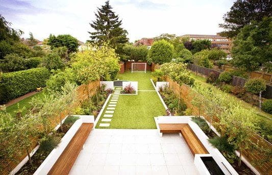 Long narrow open garden with some garden beds and stepping stones