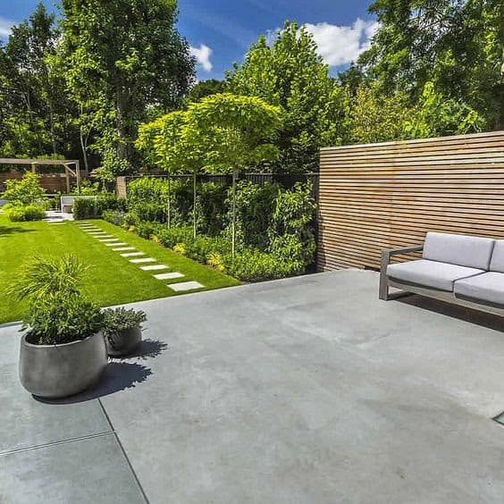 Concrete deck and grass with comfy outdoor seating