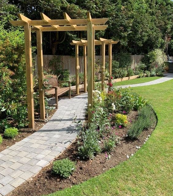 A bench and a winding path dividing the garden space