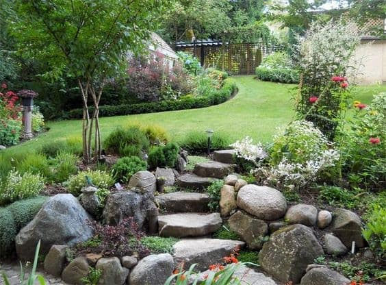 Large garden in slope with natural stone steps built into a rockery bed