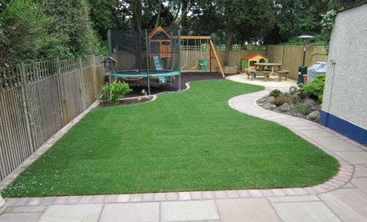 Playground in large backyard with a trampoline, swing set and Wendy house
