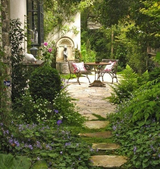 A large, beautiful garden, with a simple table and comfy chairs