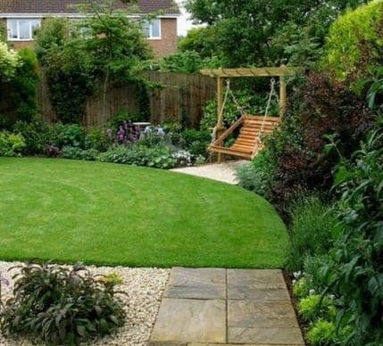 A simple garden with a wooden backyard swing