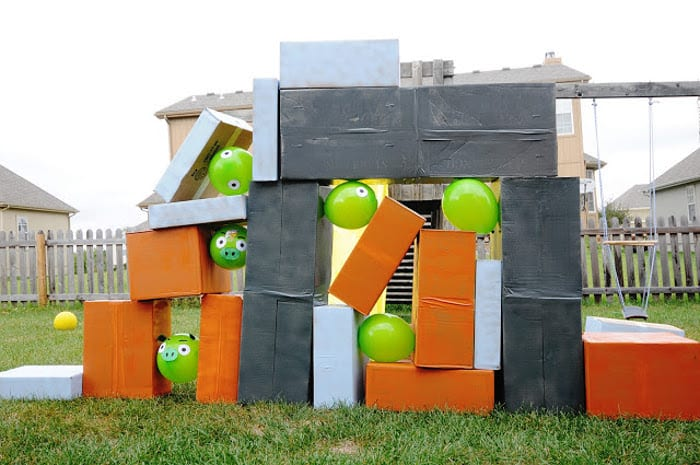 Giant angry birds made of cardboard boxes and green balloons