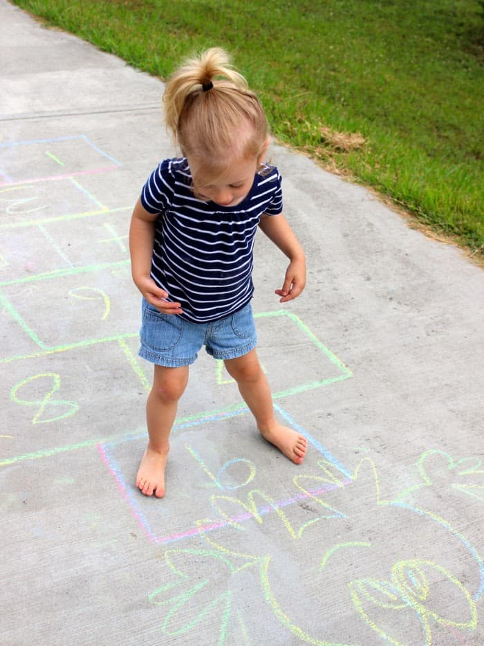 A small kid playing hopscotch in the garden