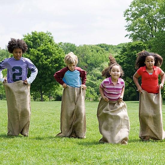 Kids playing potato sack races outdoors