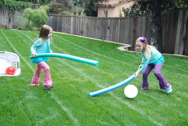 Children playing outdoor field hockey