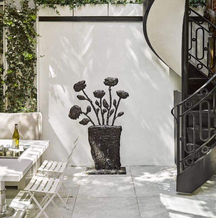 A garden sculpture against the white garden wall
