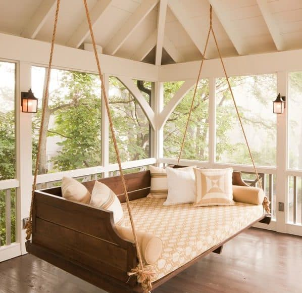 Wooden hanging bench swing with bright yellow cushions and pillows