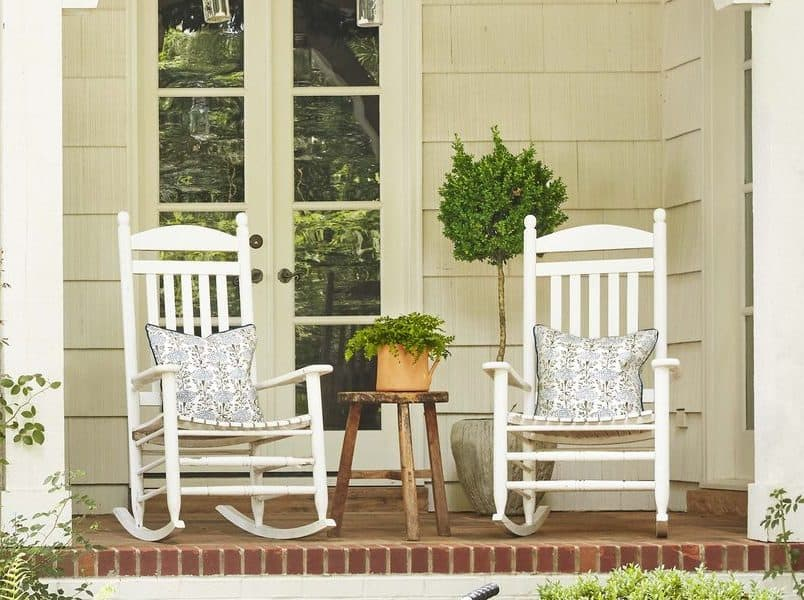 A pair of white rocking chairs placed in a front porch