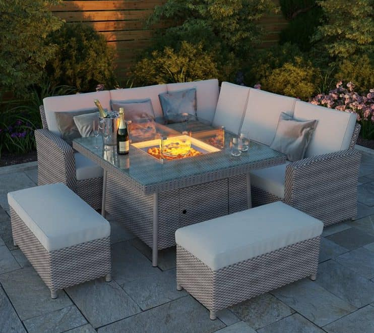 A garden dining table set with a fire pit installed in the middle