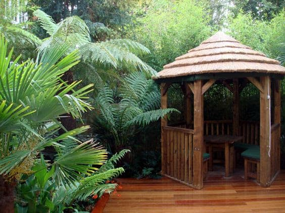 A thatched gazebo installed in a jungle-themed space