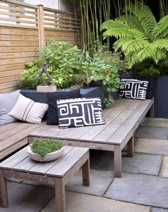 A tropical-themed corner garden with simple bench and some tropical plants