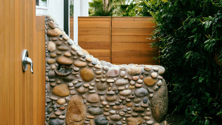 Cobble-embellished wall outdoor shower