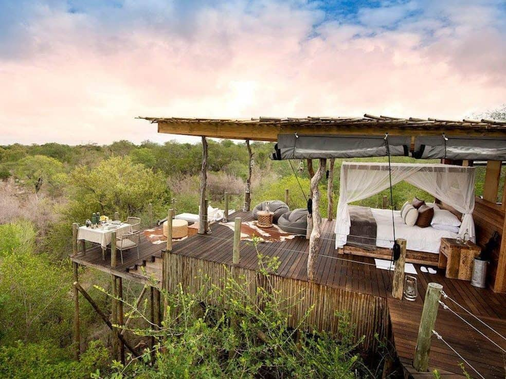 An open space treehouse sitting on a wooden deck over the African bush