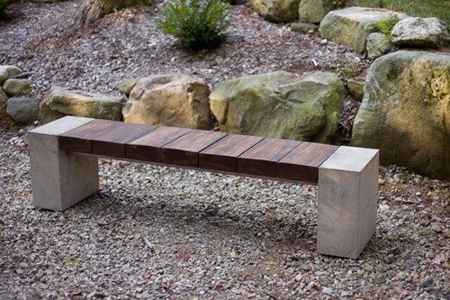 A simple garden bench made of wood, concrete, and metal materials