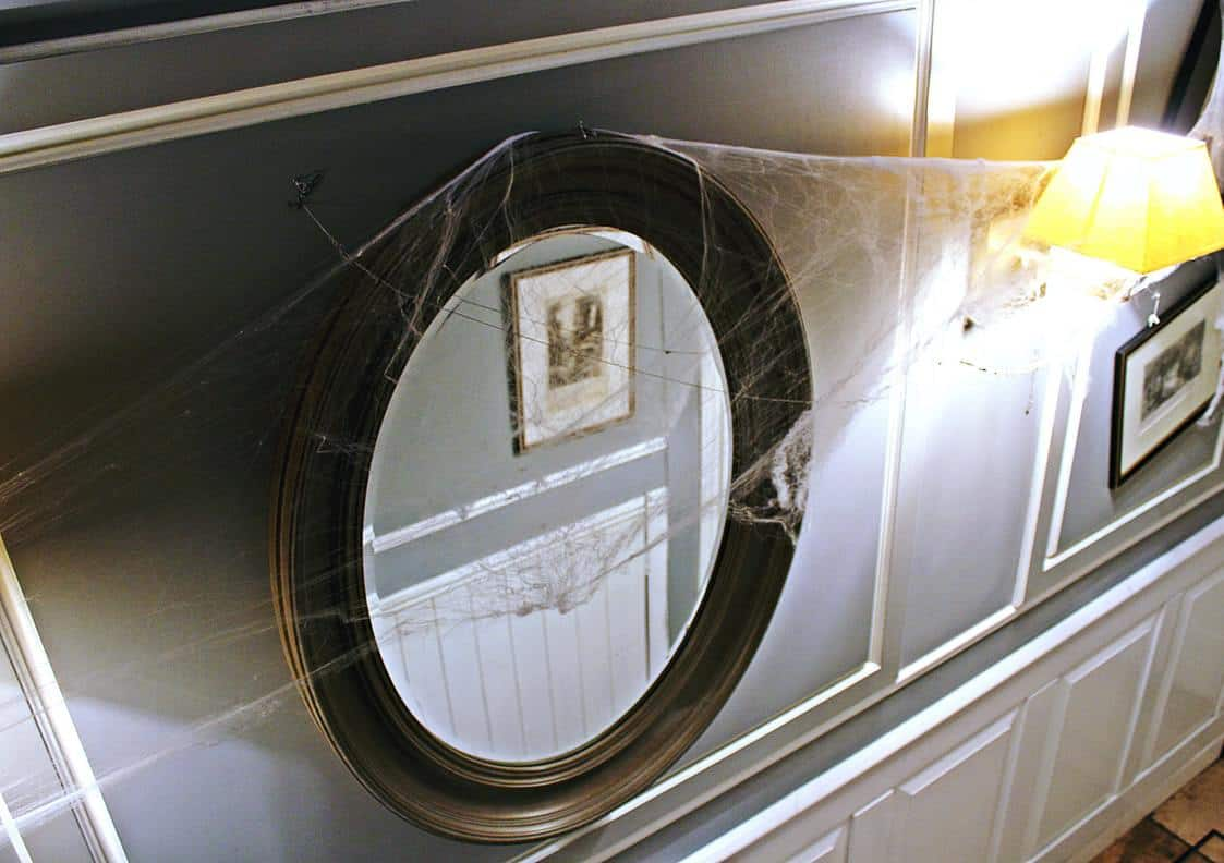 House mirror filled with spider webs