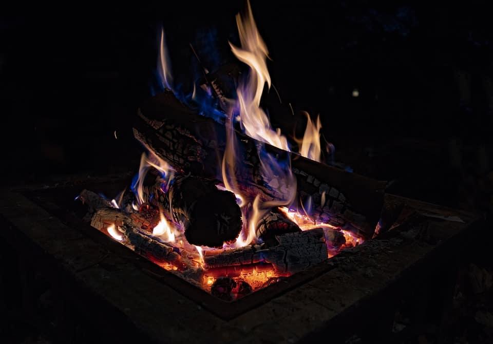 Well-lit DIY garden fire pit with firewoods