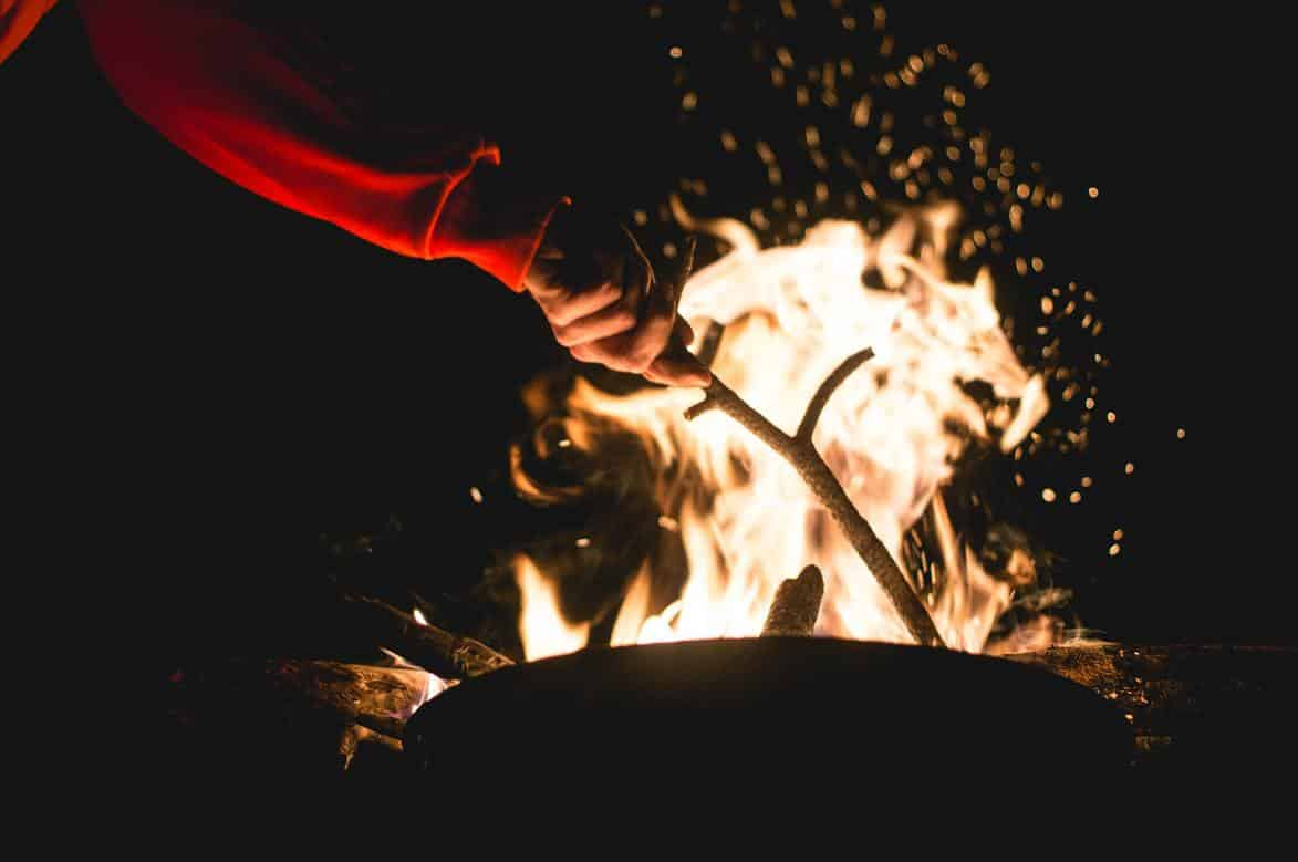A person lighting the fire pit with sticks